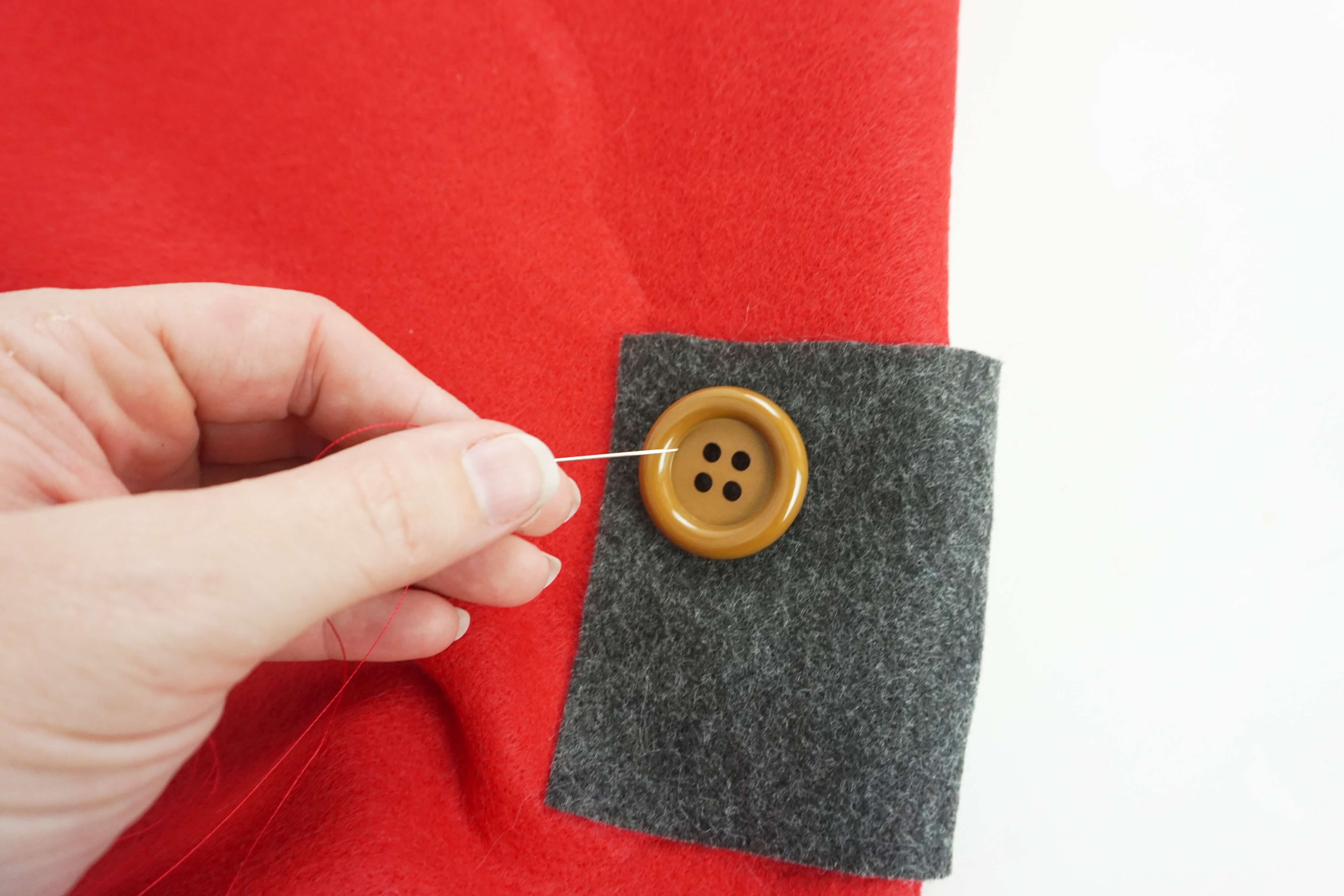 gnome costume detail of hand sewing a button onto a pocket