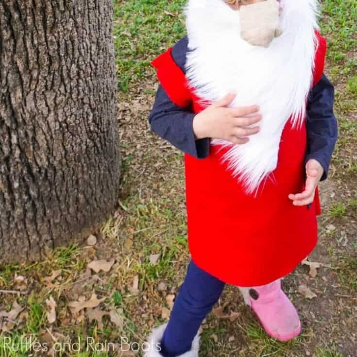 child dressed in a gnome costume standing in a yard to represent how to make a gnome costume no sew