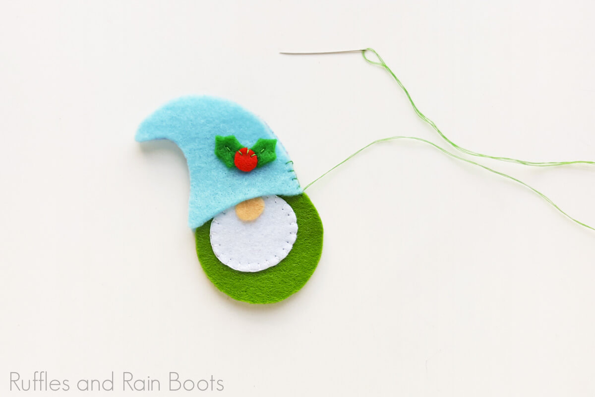 in process step of how to make a felt gnome ornament on a white background