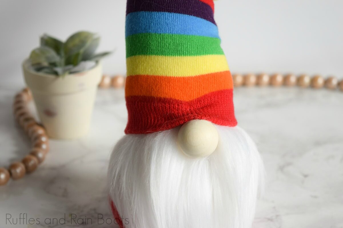 close up of Nordic gnome with a twisty hat on white background with small plant