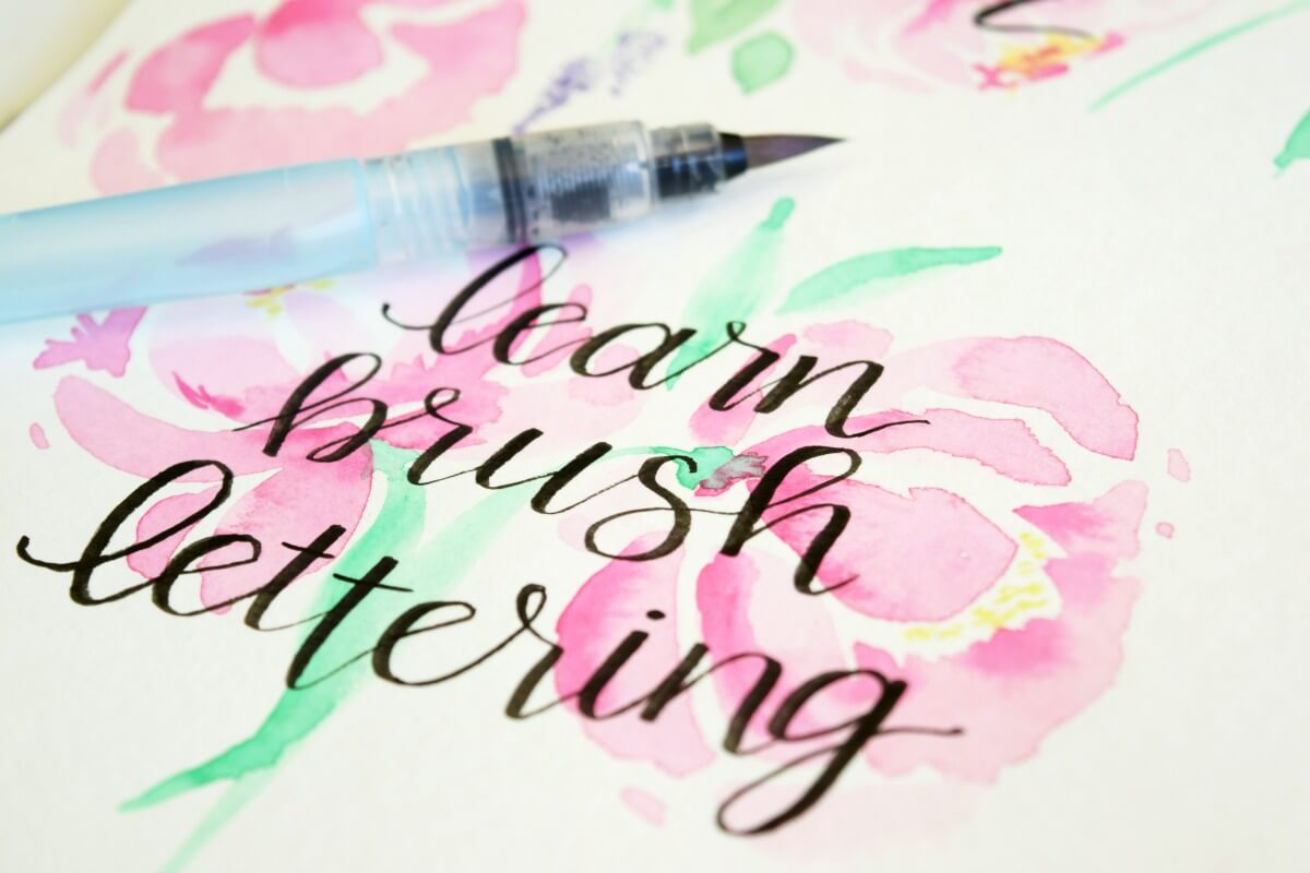 close up of brush calligraphy on floral watercolor with water brush pen