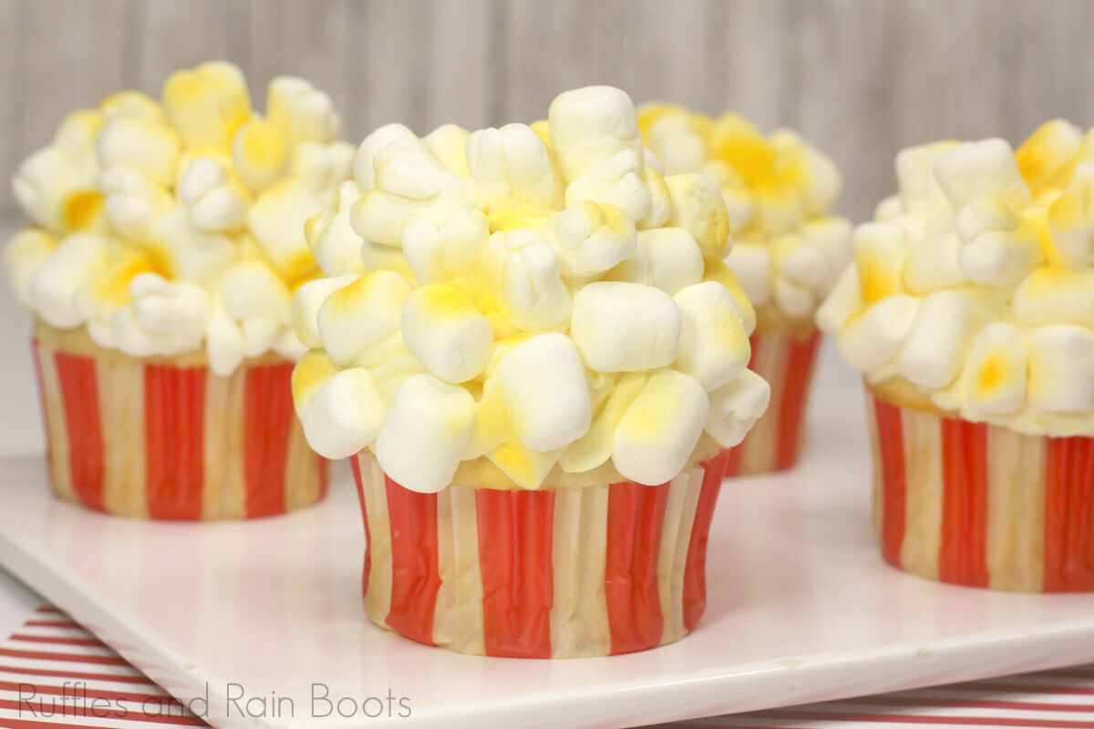 side view of popcorn cupcakes for circus party on a white cheese board on a red and white background