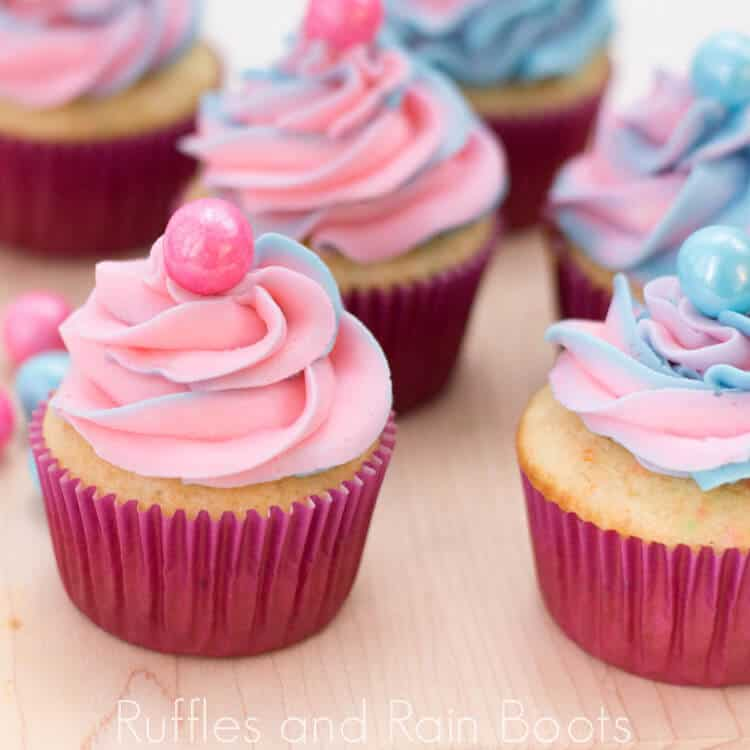 side view of cupcakes with pink and blue frosting topped with a bubblegum ball on a cutting board on a white background with pink and white striped straws and pink and blue bubblegum balls