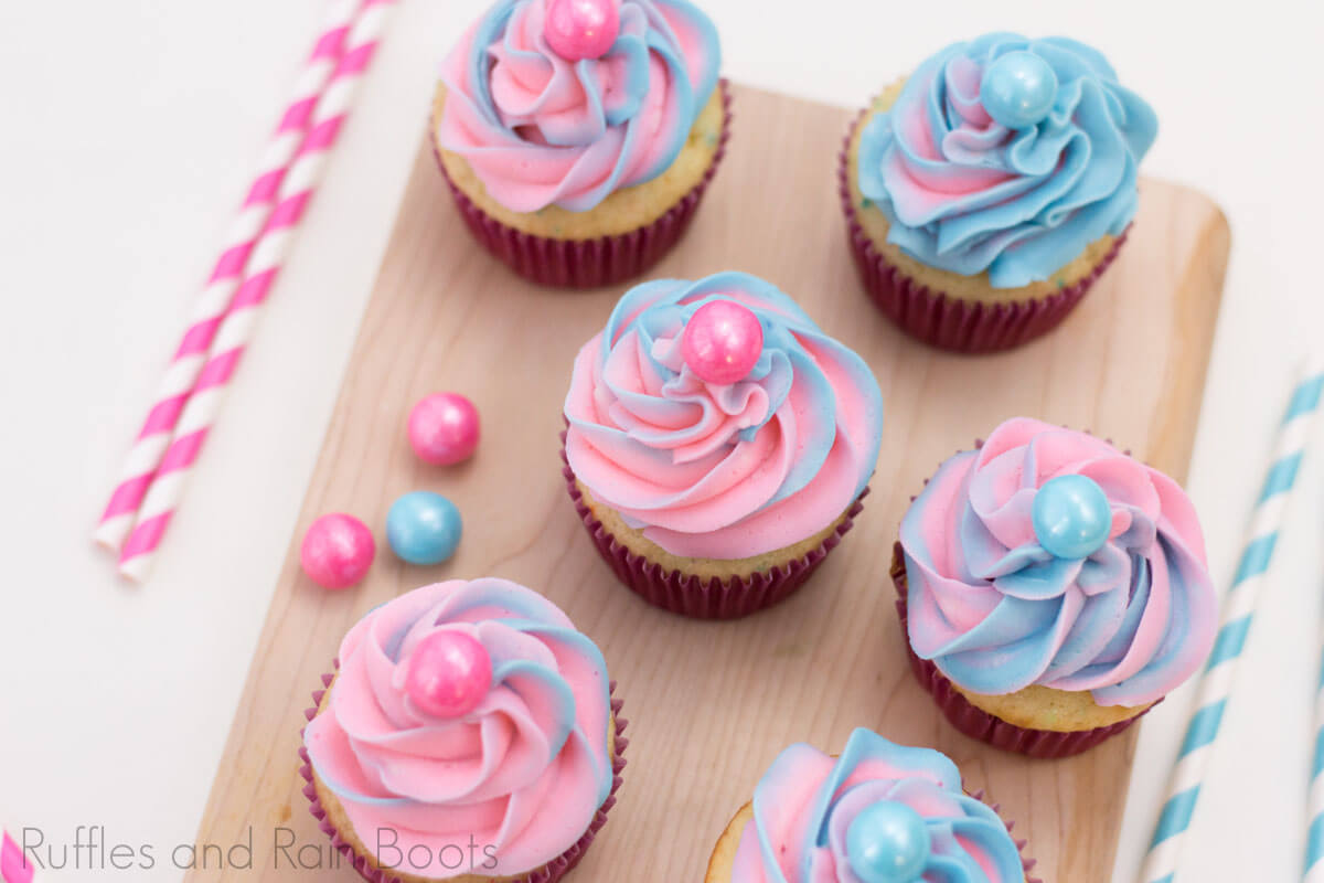 overhead view of pink and blue swirled cupcakes on a cutting board on a white background with pink and white striped straws and pink and blue bubblegum balls