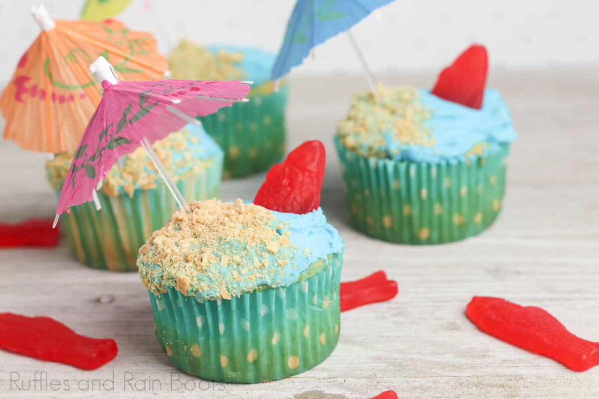 side view of ocean/beach decorated cupcakes on a light beige background with scattered red candy fish