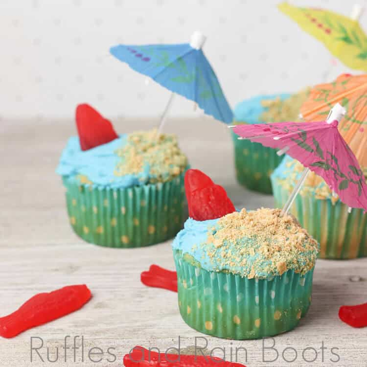 blue frosted cupcakes with green cupcake papers with tiny umbrellas and red candy fish sticking out of blue frosting on a light beige background with scattered red candy fish