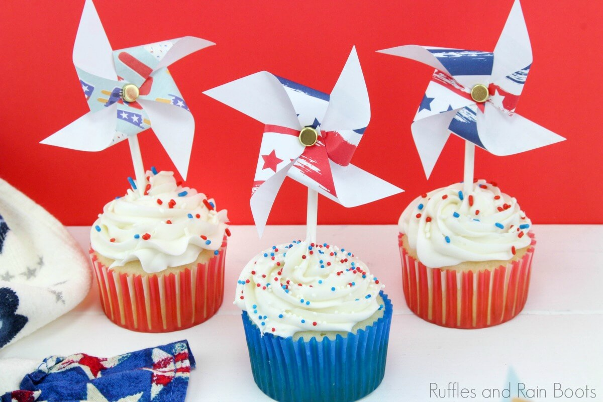 three simple 4th of July cupcakes with white icing on top and red and white cupcake liners with pinwheel toys on top on a white table with a flag linen and a red background