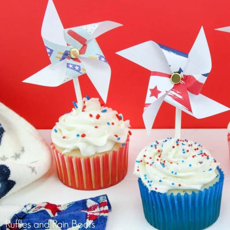 white icing on patriotic cupcakes in blue and red cupcake liners with pinwheels on sticks stuck into the top of the cupcakes on a white table with a red background