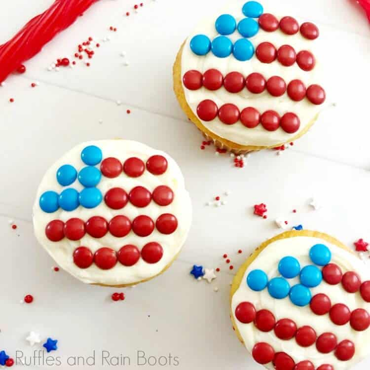 overhead view of 3 flag cupcakes, white cupcakes decorated with a flag made of candy, on a white background
