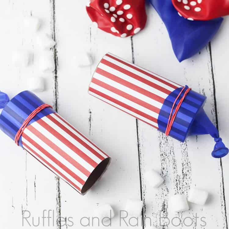 two marshmallow shooter launchers on a wooden board decorated for Independence Day celebrations