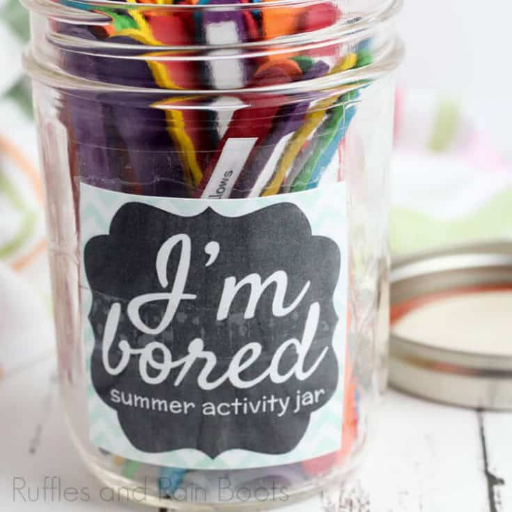 I'm bored jar for summer activity for kids on a wooden white table with lid laying nearby