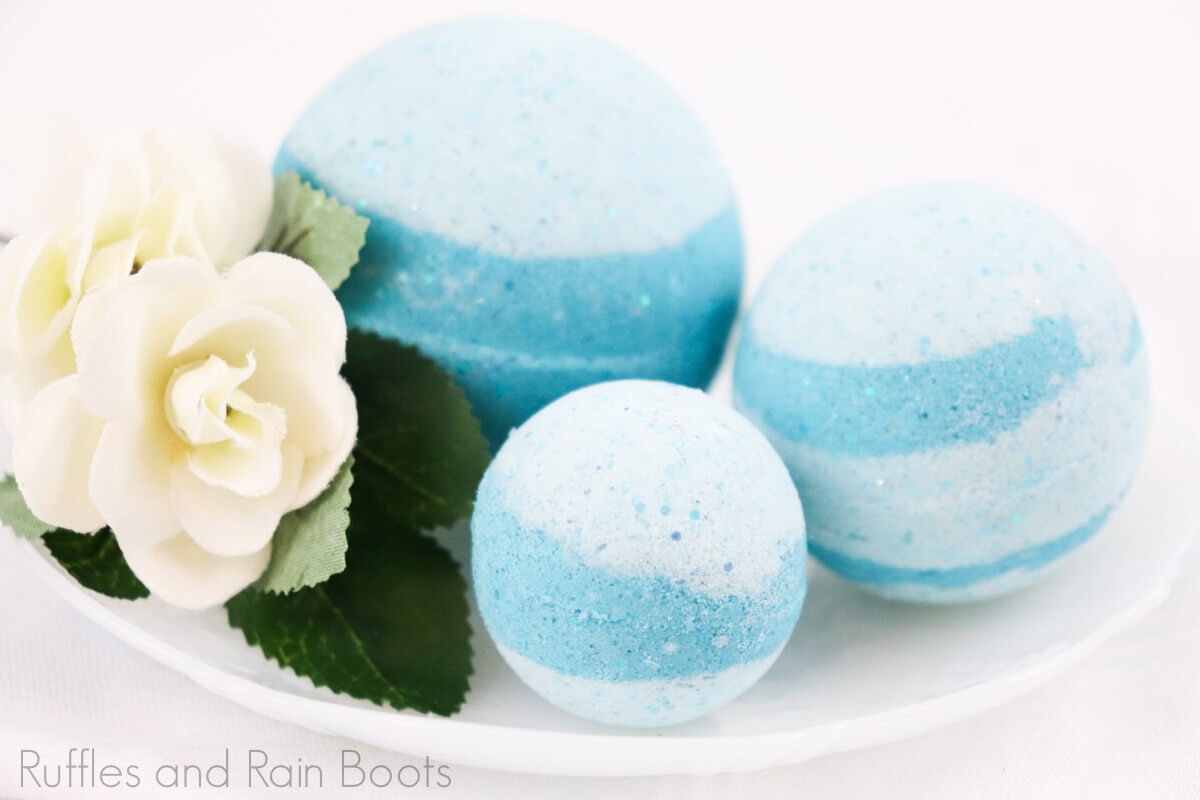 side view of simple princess jasmine bath bomb recipe sitting on a white bowl with a flower on a white background