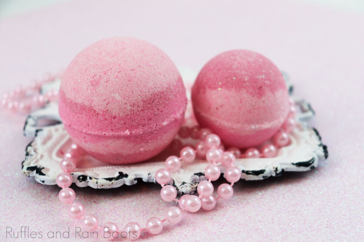 side view of two pink striped princess aurora bath bombs on a white antique square plate with toy pink beads on a pink table
