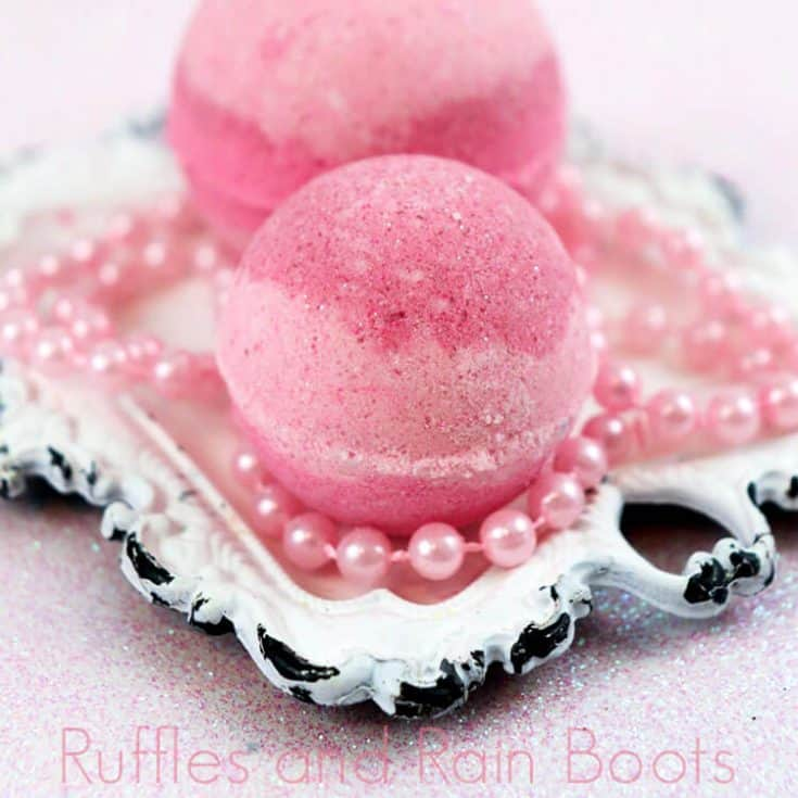 two pink striped princess aurora bath bombs on a white antique square plate with toy pink beads on a pink table
