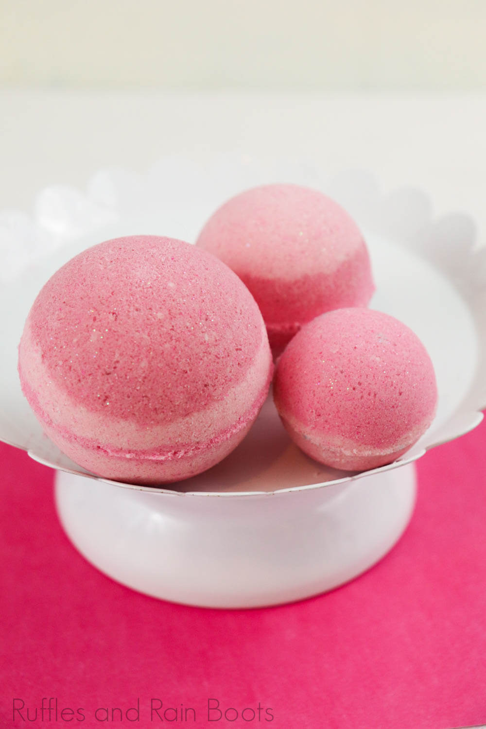 three pink sleeping beauty aurora bath bombs on a white cake stand on a pink table with a white background