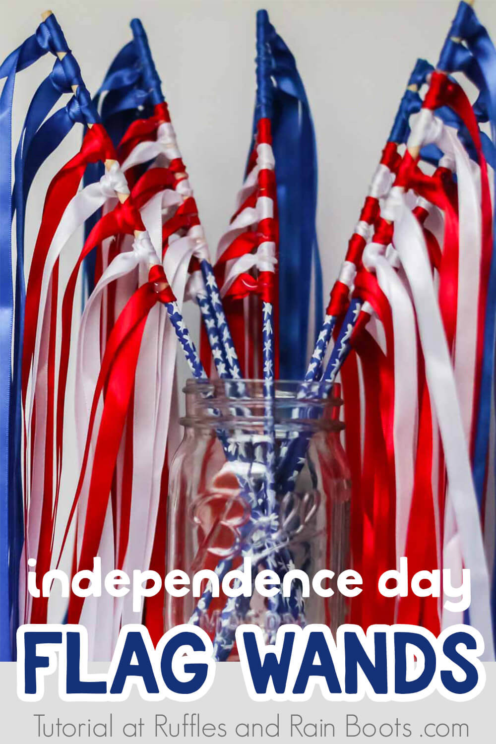 independence day flag wands with ribbon in a mason jar on a white background with text which reads independence day flag wands