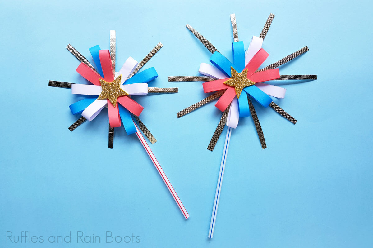 two paper firework craft for kids on a blue background