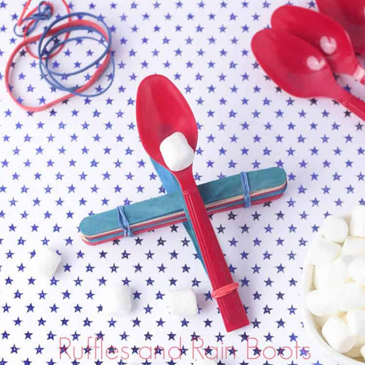 overhead view of kids marshmallow catapult on a blue and white polka dot background