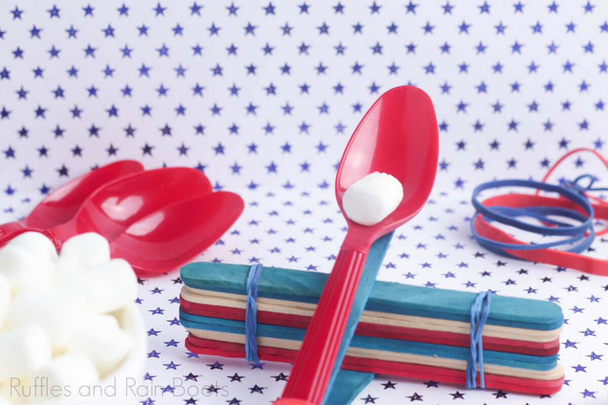 marshmallow catapults for kid science projects with spoons and popsicle sticks with marshmallows on a blue and white polka dot background