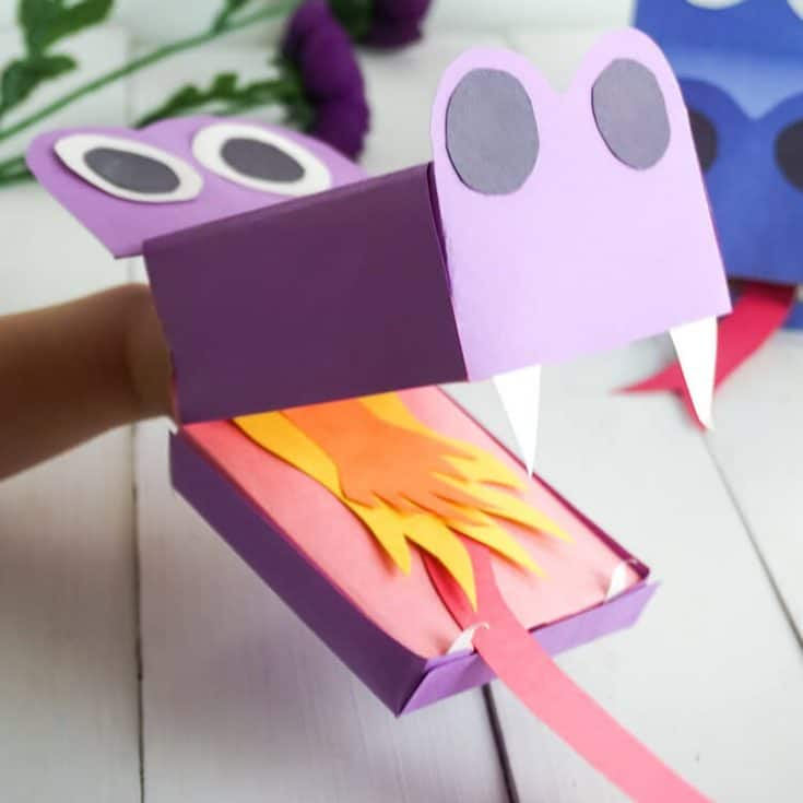 kid holding example of how to make a dragon puppet on a white wood background