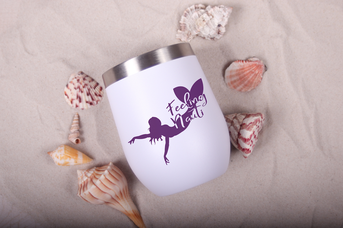 feeling nauti free mermaid svg for Cricut on a travel mug in sand with shells around it