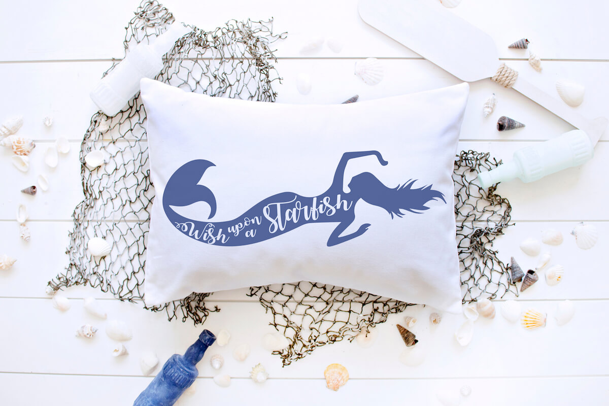 wish upon a starfish mermaid svg file on a white pillow on a fishing net on a white wood background