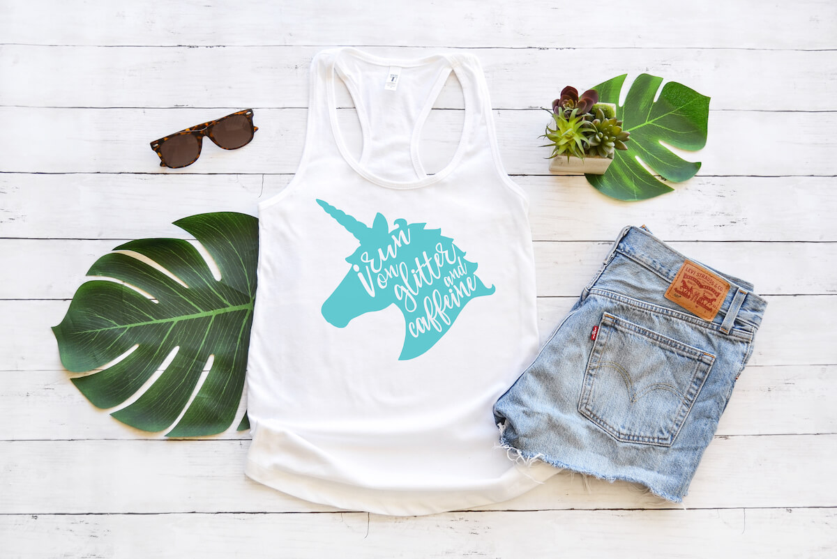 white tank top with I run on glitter and caffeine free unicorn svg graphic on a white wood background with sunglasses, leaves and jean shorts