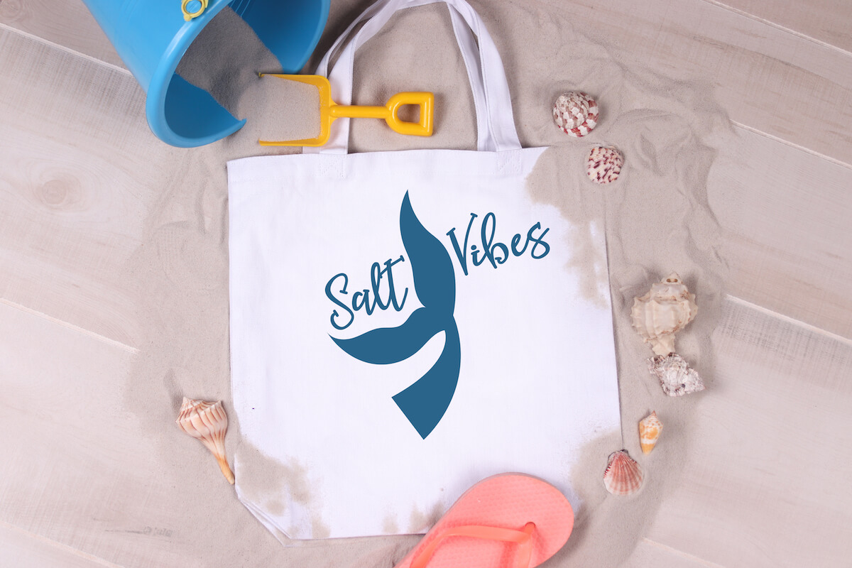 free Salt Vibes mermaid svg on beach bag on a bed of sand with flip flops, shells and kid's shovel and pail toy