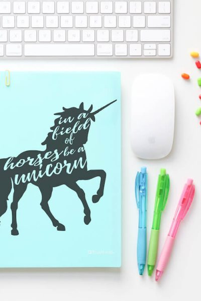 in a field of horses be a unicorn svg for silhouette on notebook on a white desk with keyboard, mouse, pens and push pens scattered around