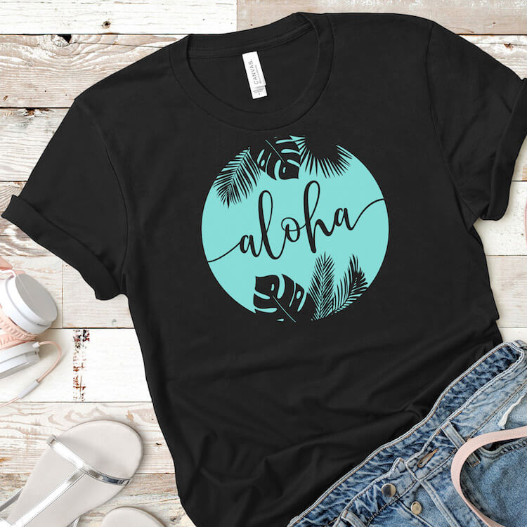 aloha free summer cut file for cricut on a black tshirt with jean shorts and headphones on a beige wood background