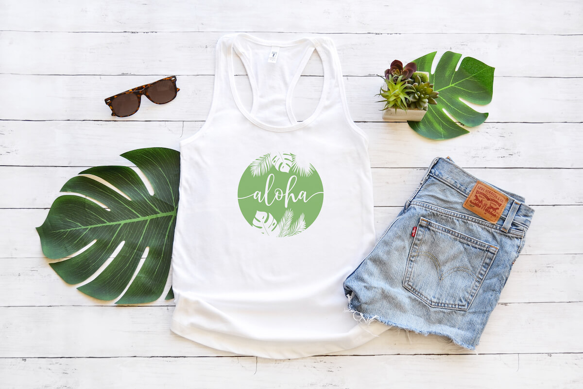 free aloha summer svg on a white tank top with jean shorts and palm leaves on a white wood background