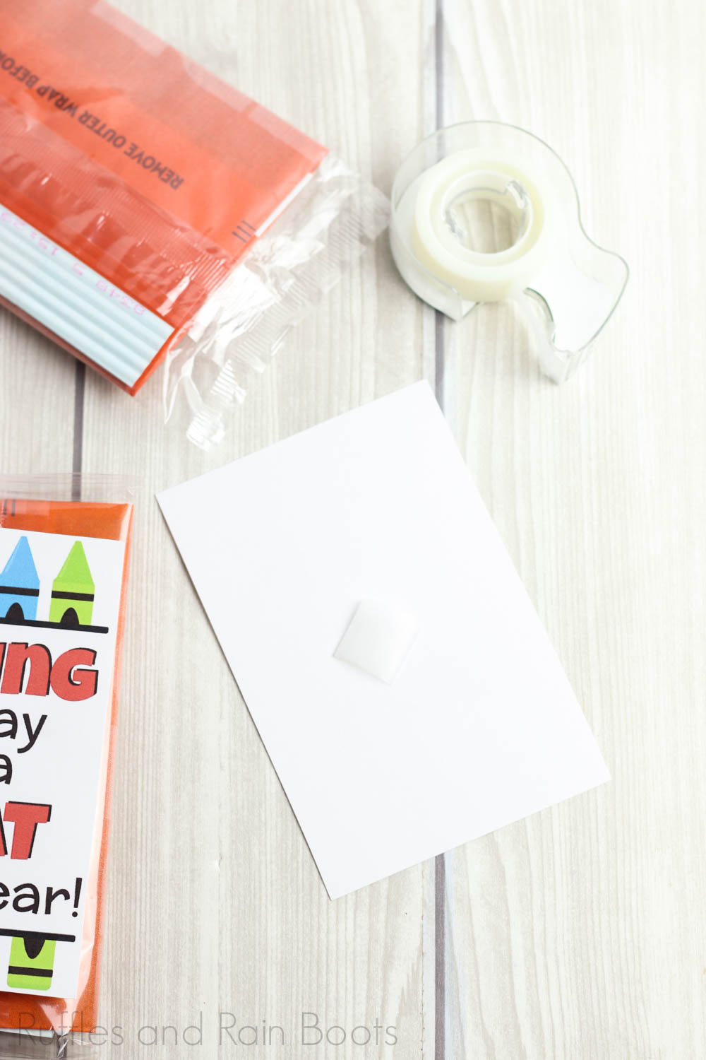 tutorial to make a simple back to school teacher gift by adding tape to back of tag for popcorn gift