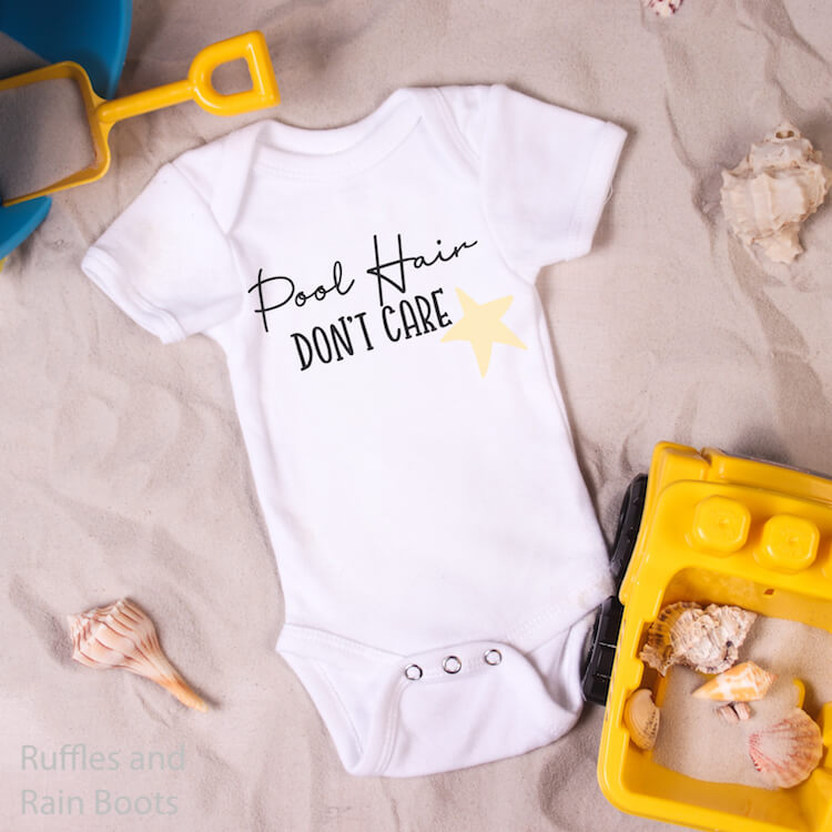Pool Hair Don't Care free summer svg for Silhouette on baby onesie next to kid toy pail and shovel and a toy dump truck with sea shells scattered around on a bed of sand