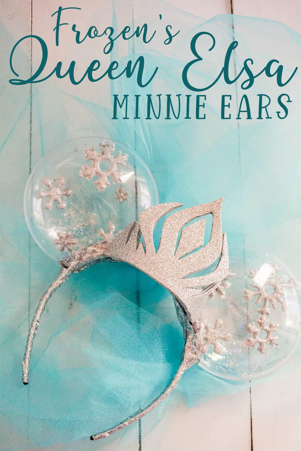 frozen queen elsa mickey ears on blue tulle on a white wood background with text wich reads frozen's queen elsa minnie ears