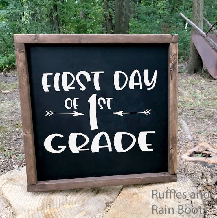 First day of First Grade back to school svg for Cricut or Silhouette on Chalkboard with a wood frame on a rock outside with trees in the background