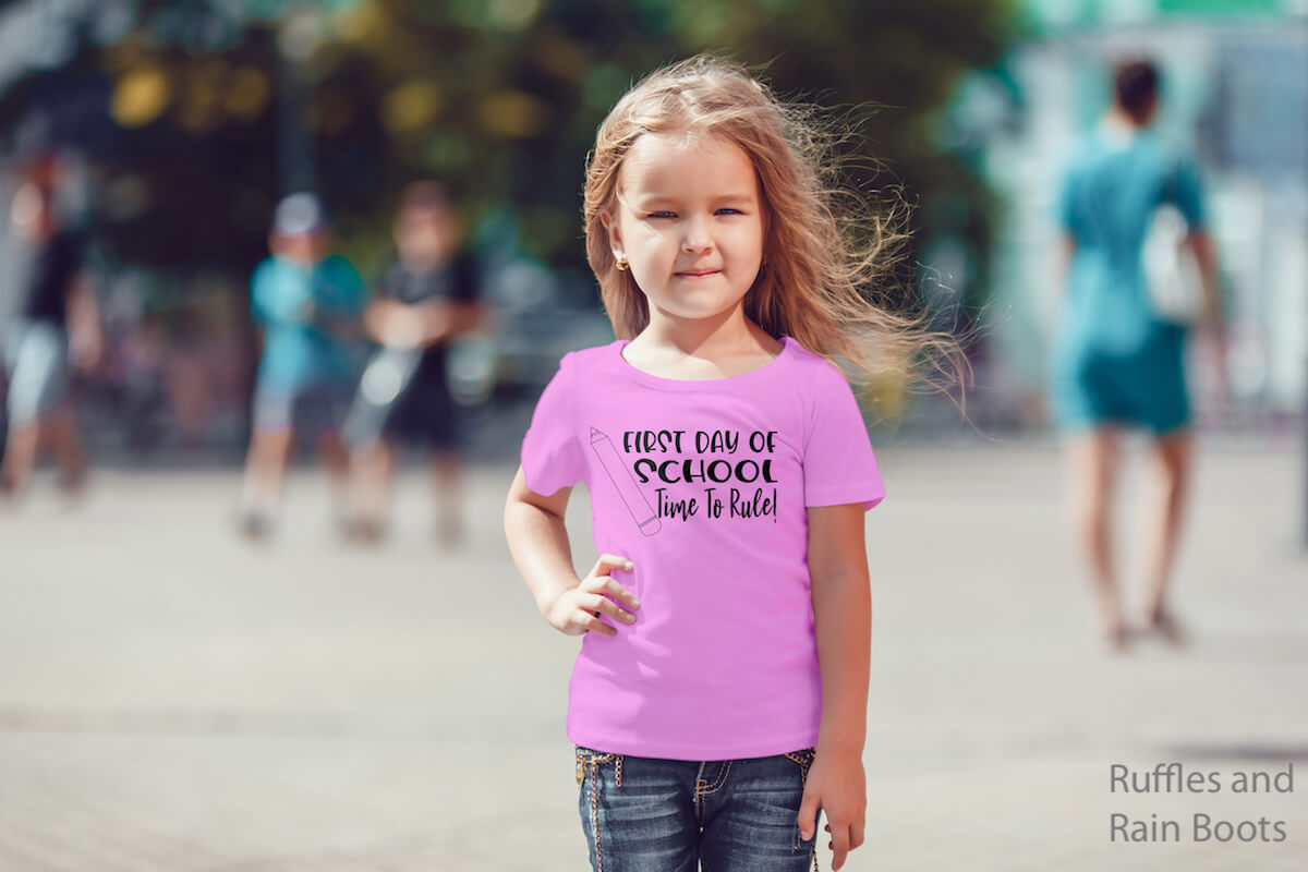 time to rule back to school svg on pink kid shirt worn by a little girl on a street with people in the background