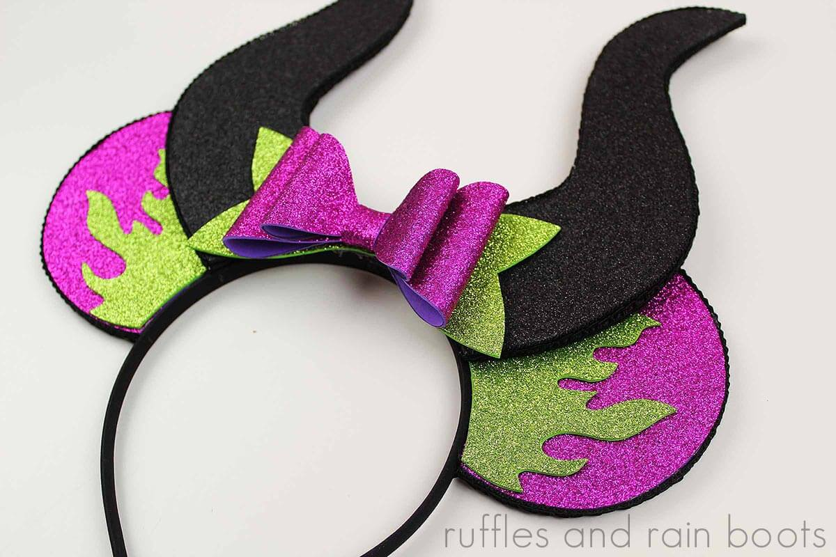 close up of green fire on purple ears with black horns to form foam Maleficent ears