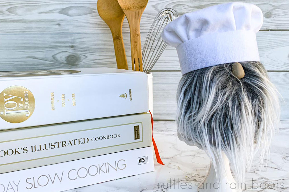 adorable chef gnome made from sock gnome body and handmade chef toque on kitchen background with cookbooks and baking utensils