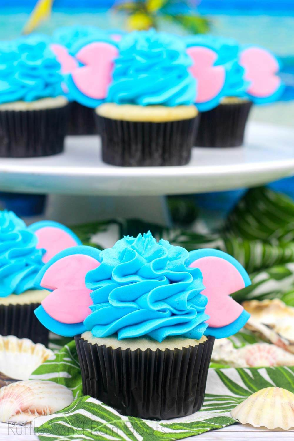 close up of buttercream frosting on cupcake with blue and pink Mickey mouse ears on white cake platter and tropical party background