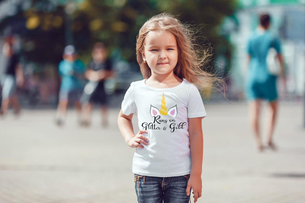 runs on glitter and gold free unicorn cut file for Cricut on kid t-shirt that a little girl is wearing while standing on a street