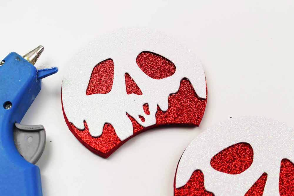 how to make evil queen poison apple mickey ears by glueing the white poison apple cutout on top of the red ear cutout