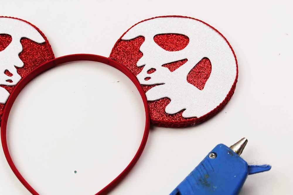 how to make evil queen poison apple mickey ears by hot gluing the ears onto the headband