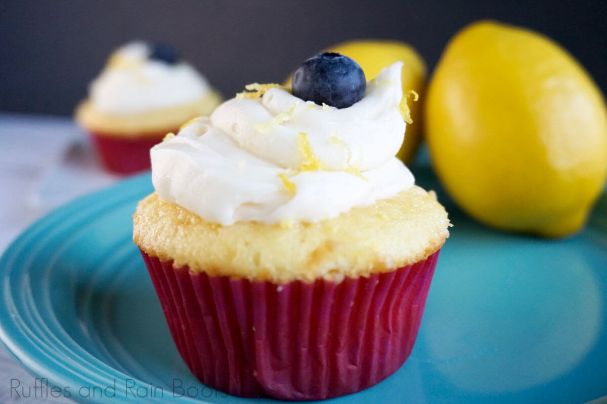 Lemon Glaze Cupcake with Light Frosting on a blue plate with lemons in the background