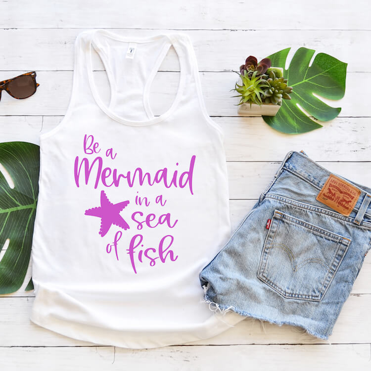 Be a Mermaid in a Sea of Fish free mermaid svg file for cricut on tank top with jean shorts and tropical leaves on a white wood background