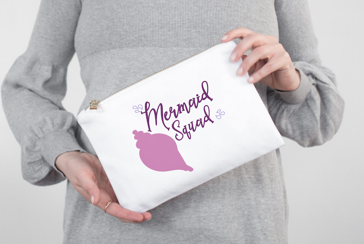 Mermaid Squad free cut file for silhouette on hand bag held by a lady in a grey dress in the background