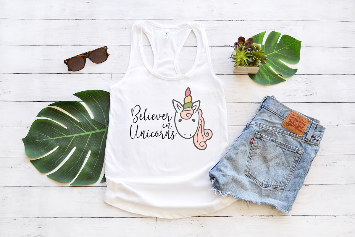 Believer in Unicorns free unicorn svg on tank top with jean shorts and palm leaves on a white wood background