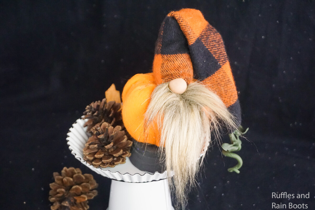 how to make a fall gnome with a pumpkin shape on a white cupcake stand with pinecones on a black background