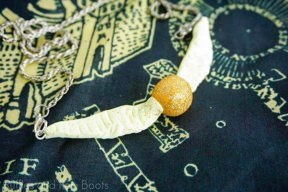 Fun Golden Snitch Necklace from Polymer Clay on a black background