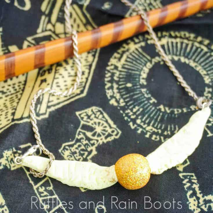 Golden Snitch Necklace Clay on a black background with a wand