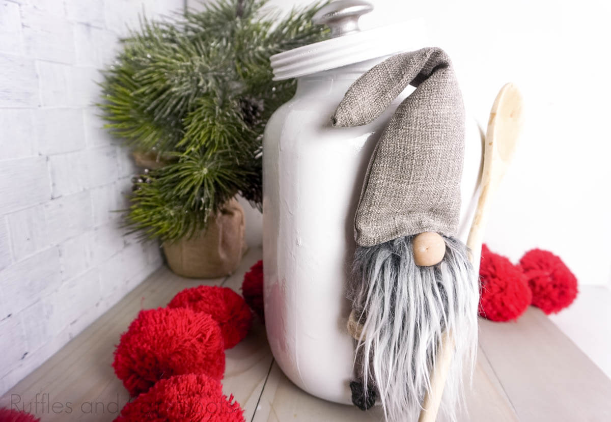 DIY Adorable Gnome Cookie Jar Upccyle on a white wood background witha christmas tree behind it